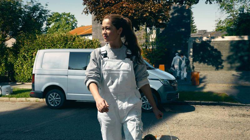 Eine Malerin läuft zur Kamera. Im Hintergrund ein Volkswagen Transporter.