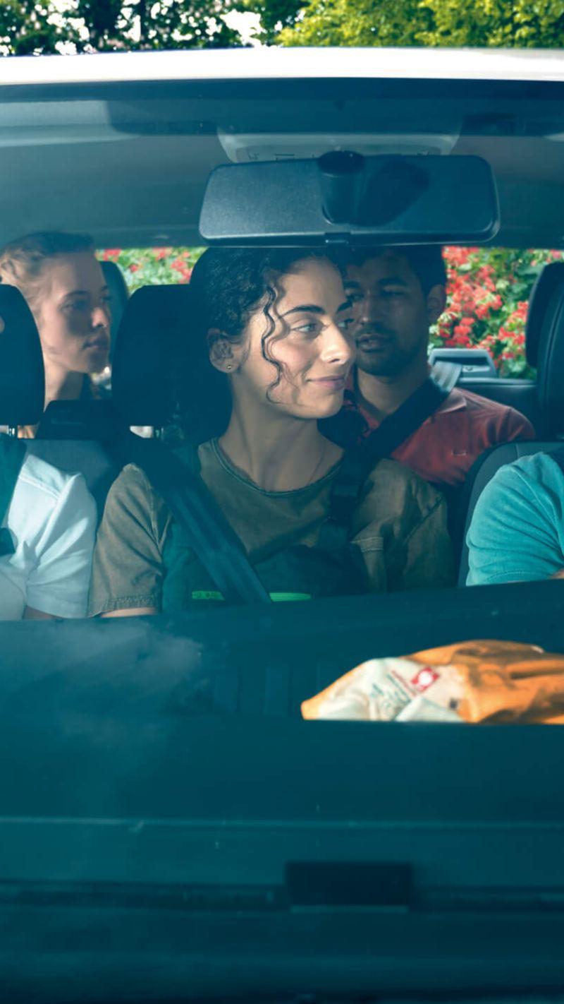 Eine Gruppe von Arbeiterinnen und Arbeitern im Blaumann sitzen in einem Volkswagen Nutzfahrzeug.