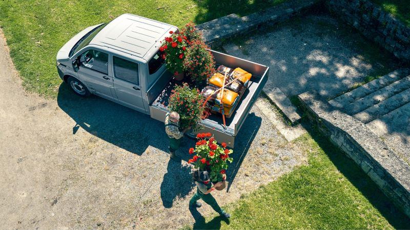Zwei Gärtner entladen einen Volkswagen Nutzfahrzeuge Pritschenwagen.