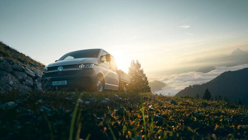 vw Volkswagen Transporter pickup kjører i skråning med fjell i bakgrunn, solskinn og gress
