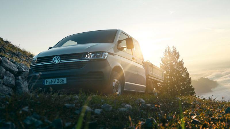 vw Volkswagen hvit Transporter 6.1 pickup kjører på fjellet i solnedgang dobbeltkabin doka pickupplan