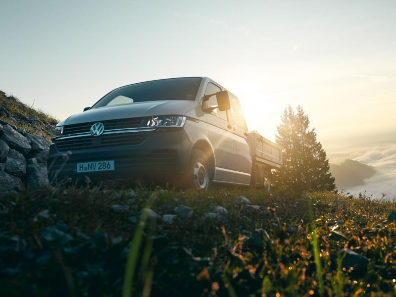 The Transporter 6.1 Dropside Van stands on a mountain above the clouds.