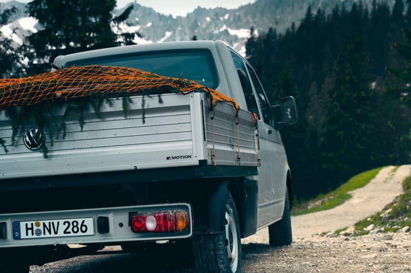 Ein Transporter 6.1 Pritschenwagen auf einem Feldweg.