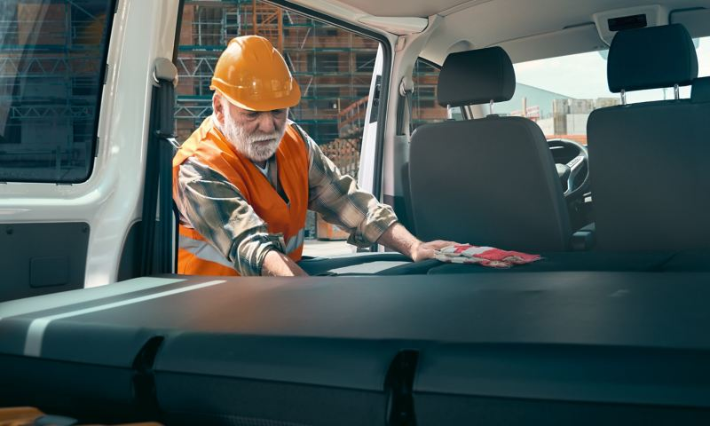 A worker is reaching into the Volkswagen Transporter 6.1 Kombi.