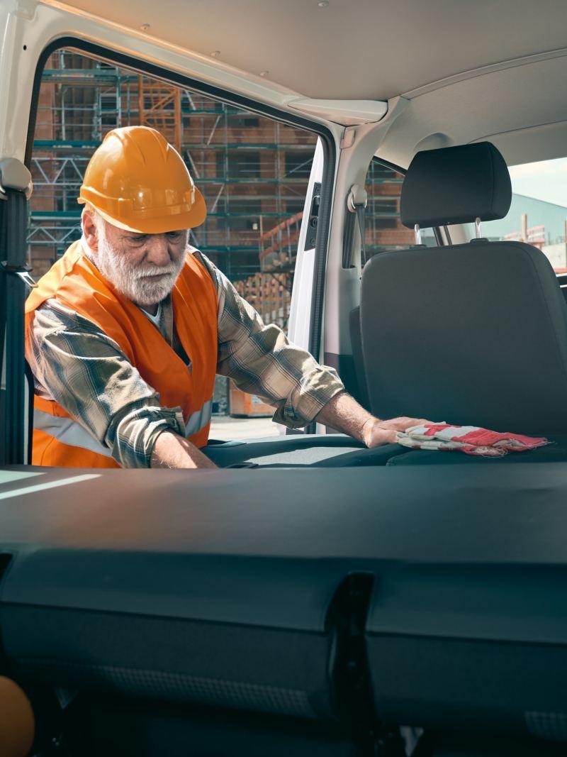 A worker is reaching into the Volkswagen Transporter 6.1 Kombi.