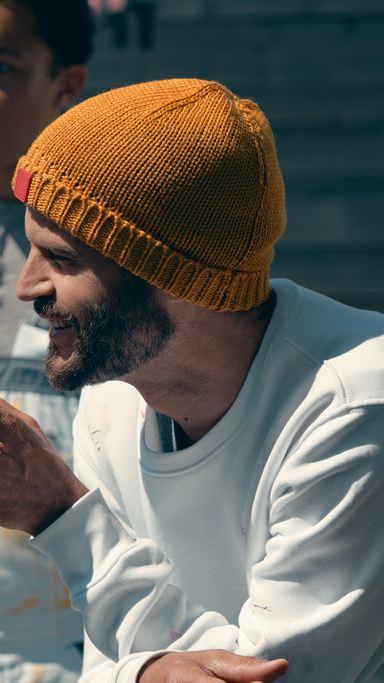 En maler med skjegg som smiler og snakker med kollegaer i ført hvite klær og strikket lue i okergul