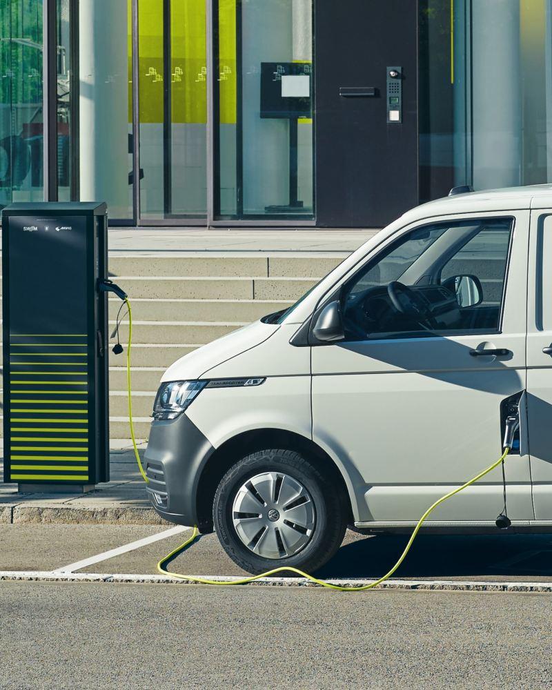 Ein VW ABT e-Transporter wird an einer Ladesäule aufgeladen.