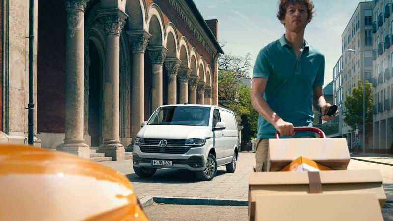 In primo piano un fattorino che consegna alcuni pacchi, dietro un Transporter Furgone parcheggiato a bordo strada visto frontalmente.