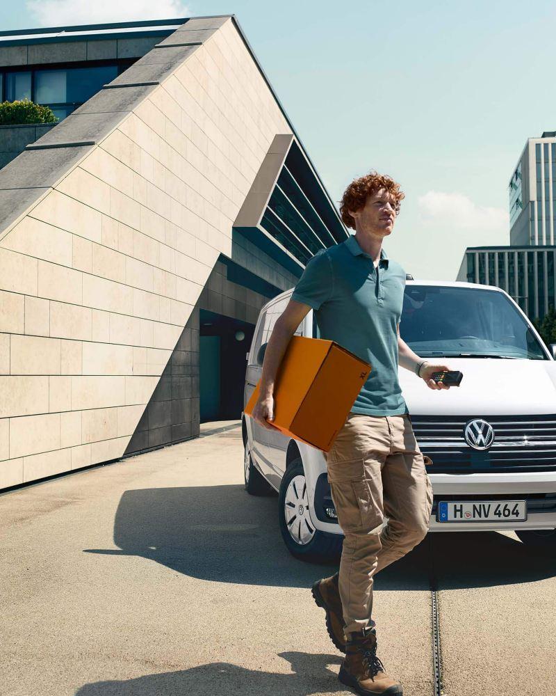 Ein Mann stellt ein Paket zu, sein Transporter seht im Hintergrund.