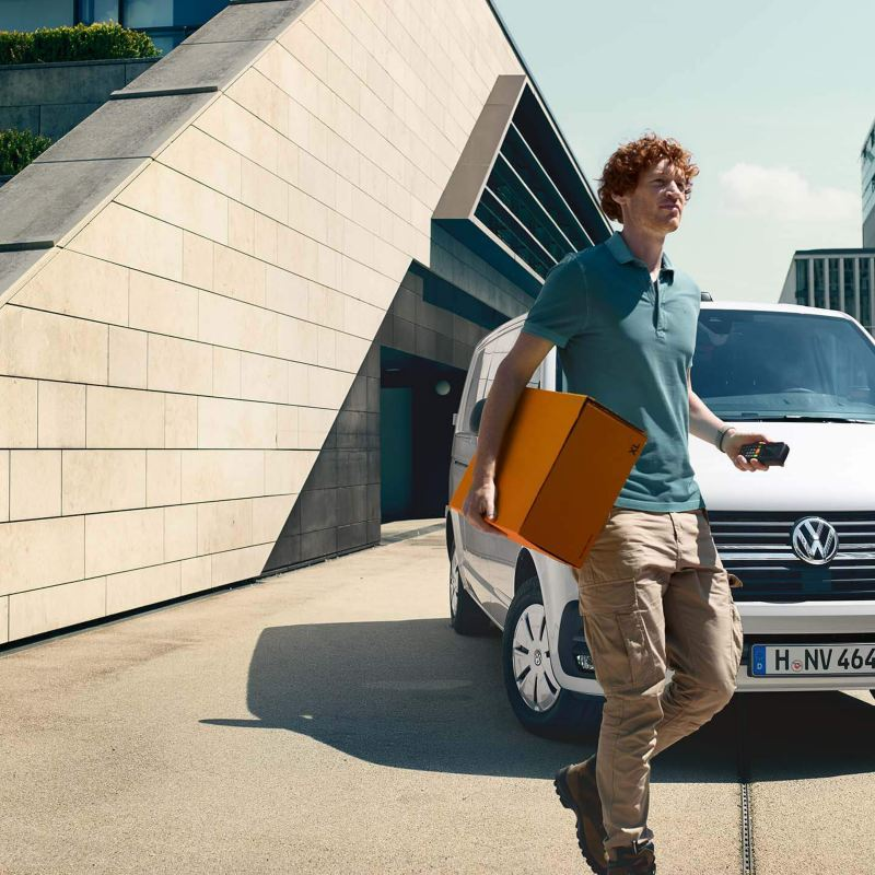 Ein Kurier stellt mit seinem Volkswagen Transporter Pakete zu.