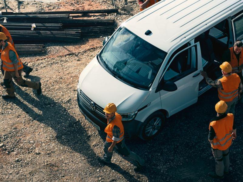 Einige Bauarbeiter stehen auf einer Baustelle um ihren Volkswagen Transporter 6.1 Kombi.