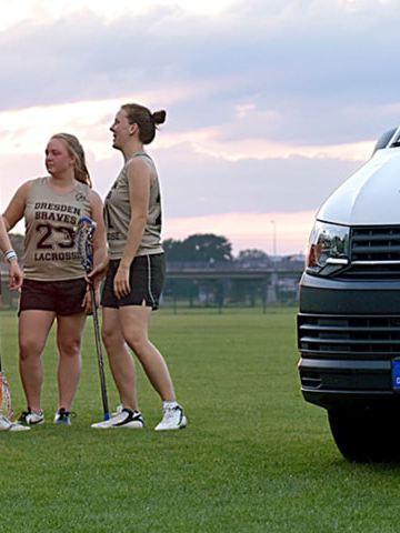 Ein Bulli von CarlundCarla.de steht auf einem Lacrosse-Feld. Im Hintergrund ist eine Damenmannschaft zu sehen.