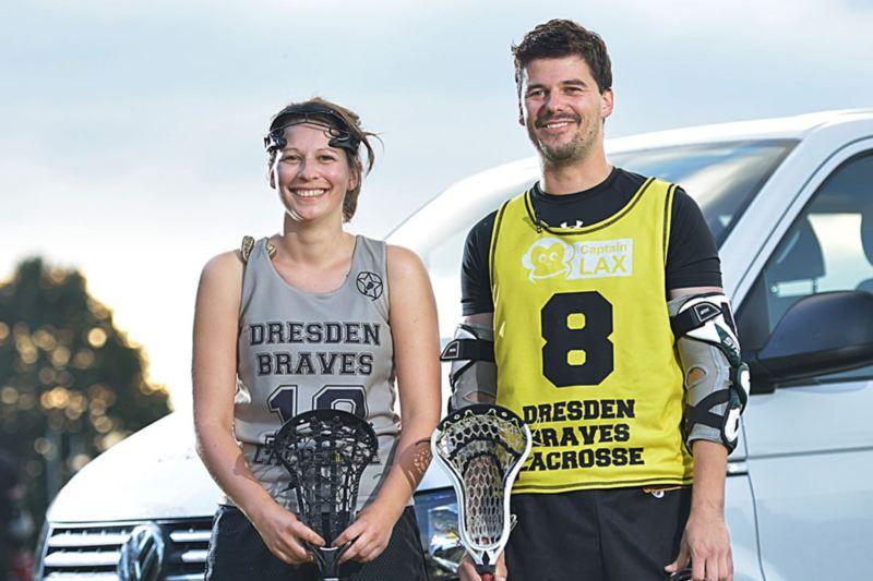 Zwei Lacrosse-Spieler stehen vor einem Volkswagen Nutzfahrzeuge Transporter.