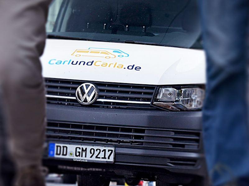Ein Bulli von CarlundCarla.de fährt eine belebte Straße entlang.