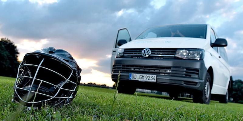 Ein Volkswagen Nutzfahrzeuge Transporter steht auf einem Lacrosse-Feld. Im Vordergrund ist ein Lacrosse-Helm zu sehen.