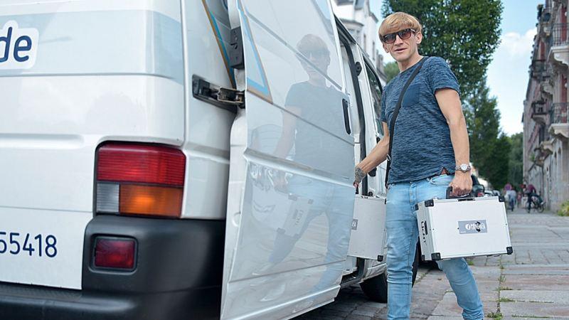 Ein Kunde von CarlundCarla.de lädt sein DJ Equipment in sein gemietetes Volkswagen Nutzfahrzeug.