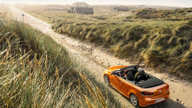 Volkswagen cabrio naranja por un camino de playa con chalets al fondo
