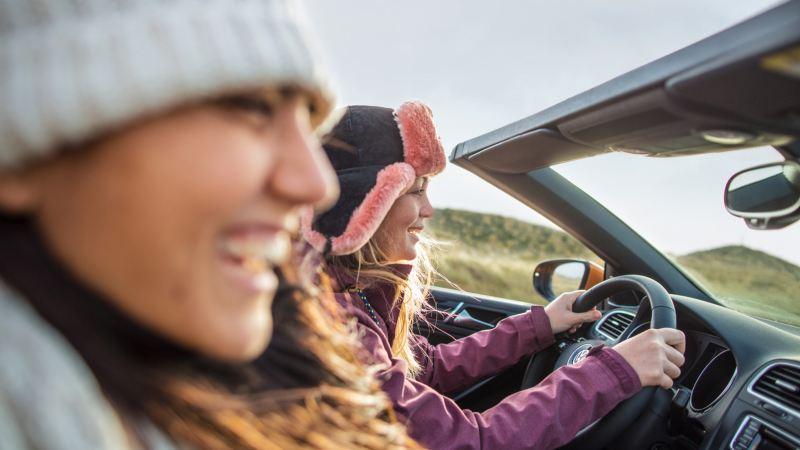 Dos chicas jóvenes sonriendo y conduciendo un Volkswagen cabrio