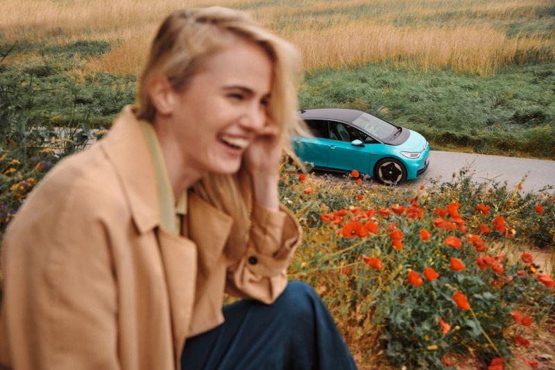 Volkswagen ID.3 en una carretera detrás de una chica sonriendo sentada en un campo de flores