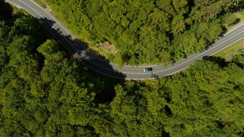 Vista aérea: Un coche circulando por una carretera a través de un bosque.