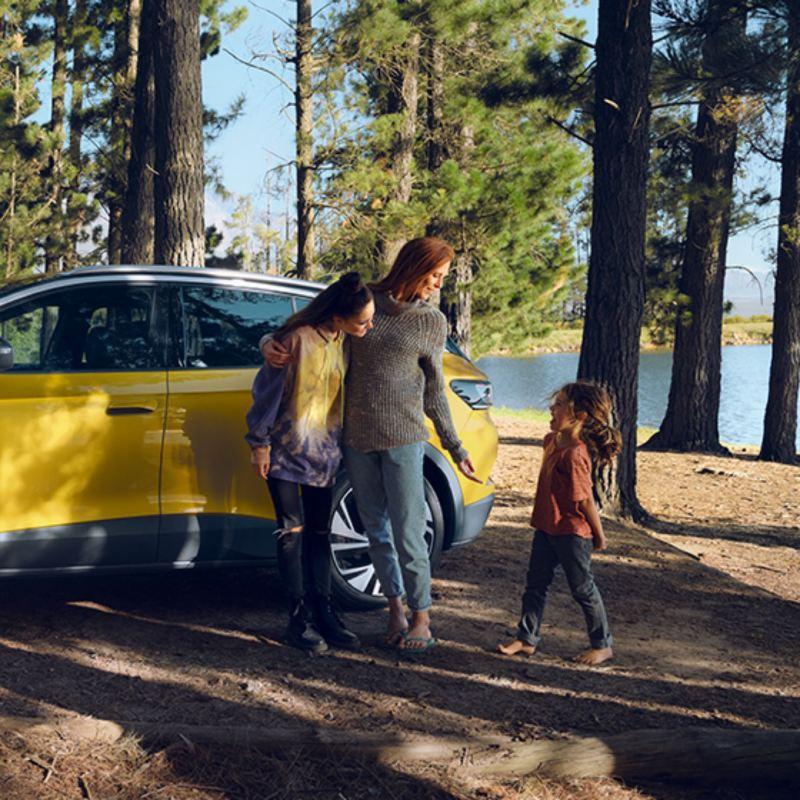 Madre con dos hijas de pie delante de un Volkswagen ID.4 amarillo aparcado en un bosque de pinos.