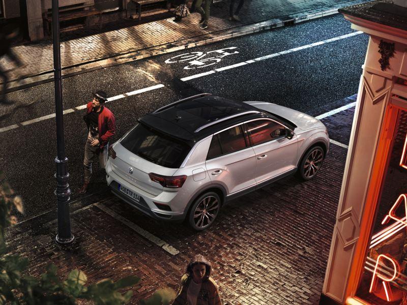 Volkswagen T-Roc blanco visto desde arriba aparcado en la ciudad de noche