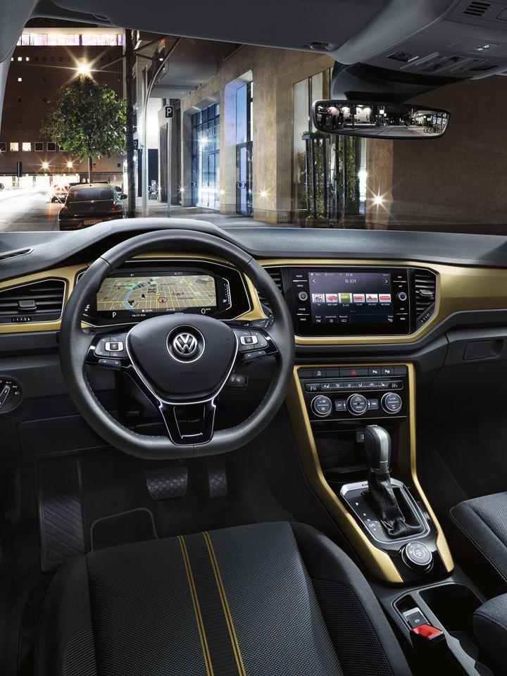 Vista del puesto de conducción y la iluminación interior de un Volkswagen T-Roc de noche en la ciudad