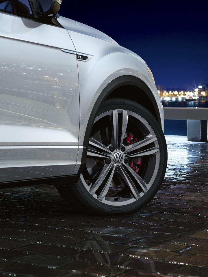 Detalle de las llantas de un Volkswagen T-Roc blanco con vista a una ciudad de noche al fondo