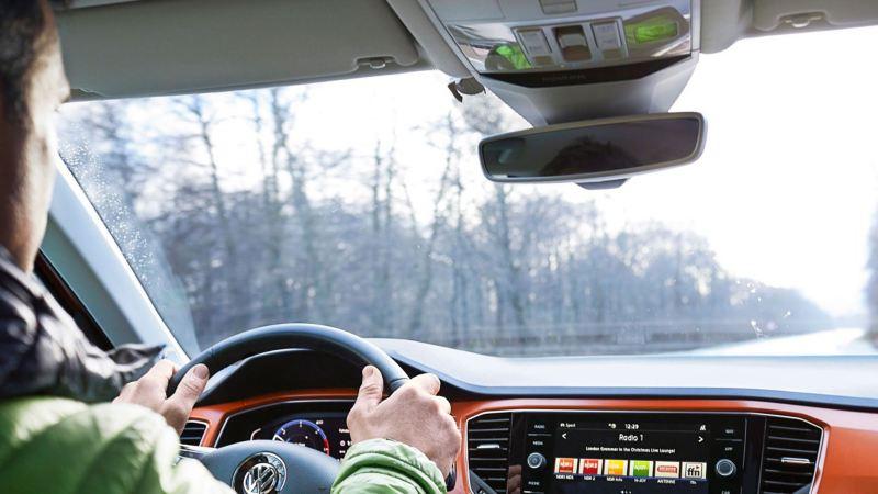 Vista desde el interior de un Volkswagen hacia la carretera, se ve parcialmente al conductor y el salpicadero