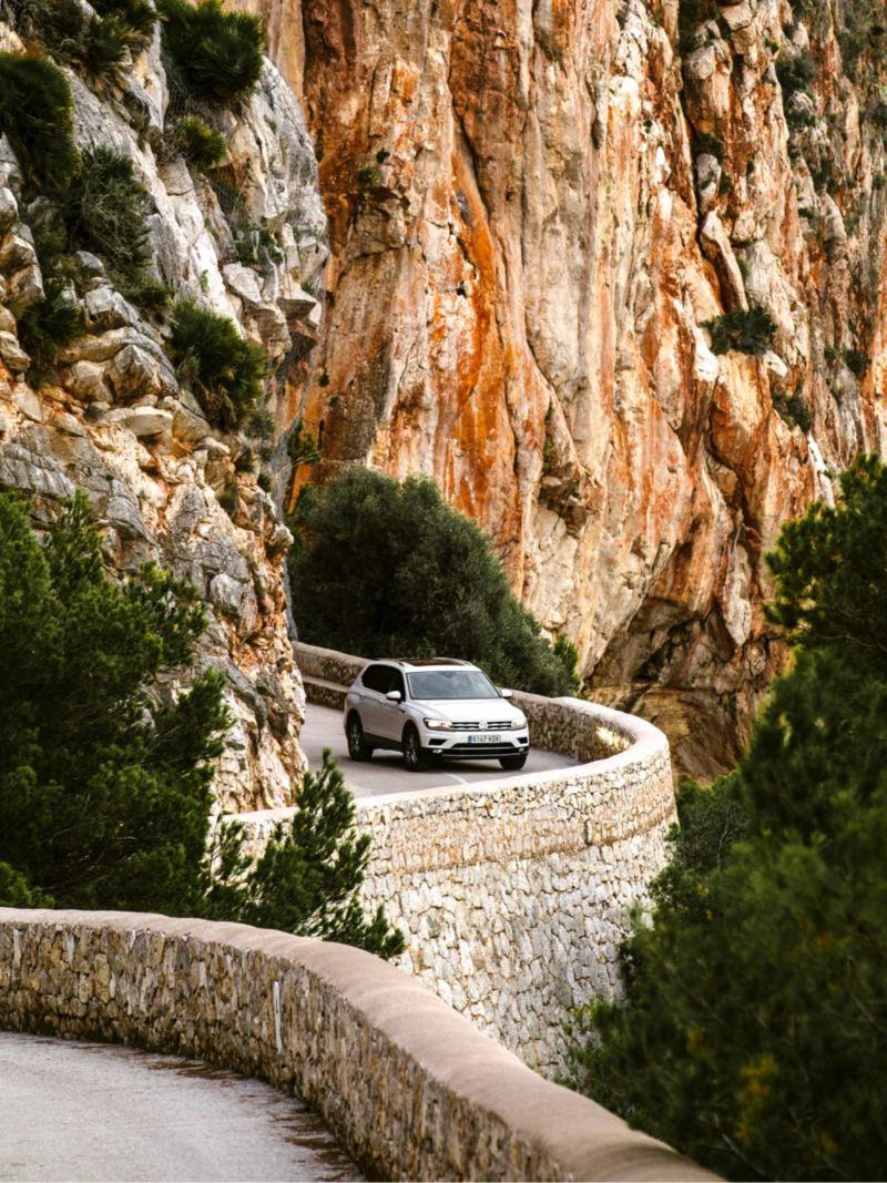 Volkswagen Tiguan circulando por una carretera de montaña junto a unos riscos