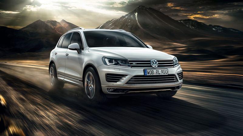 SUV Volkswagen circulando por una carretera de tierra al atardecer con unas montañas al fondo