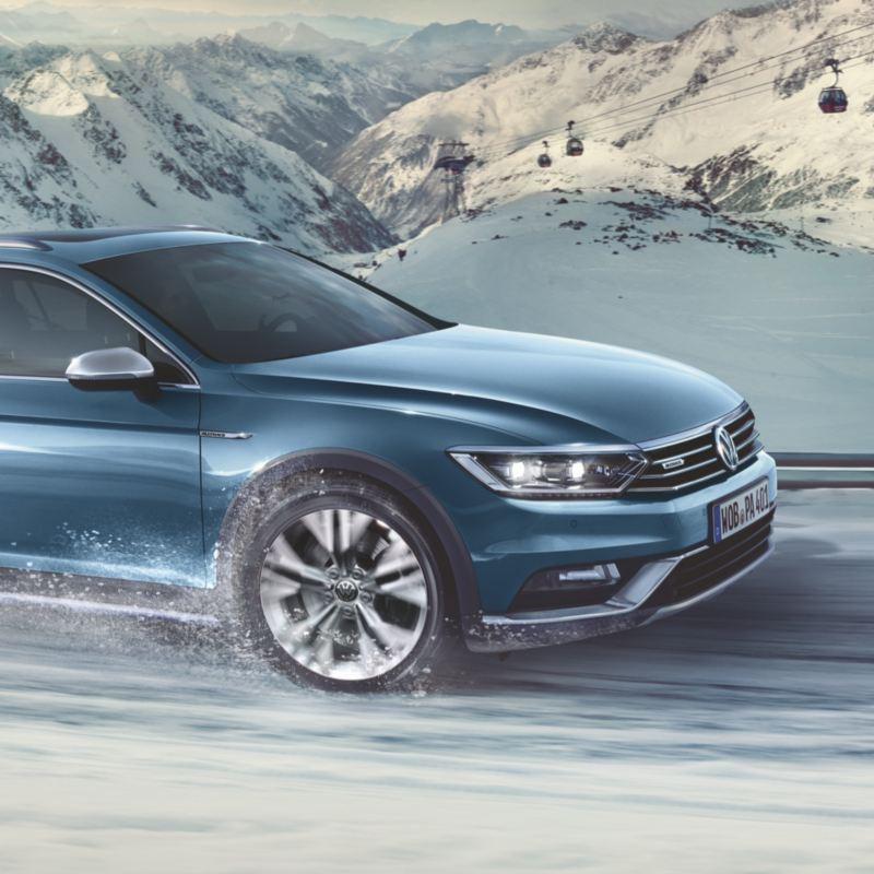 Vista de la parte delantera de un Volkswagen circulando por una carretera de montaña nevada con vistas a un teleférico detrás
