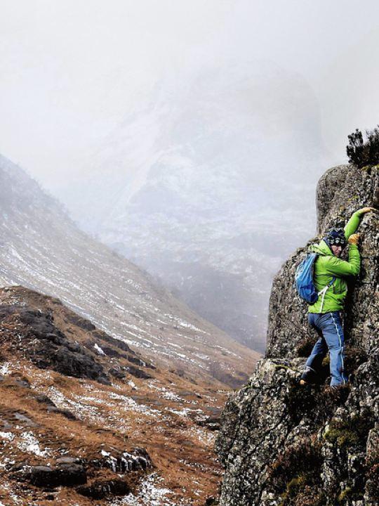 Hombre escalando una pared de roca en medio de la montaña un día nublado