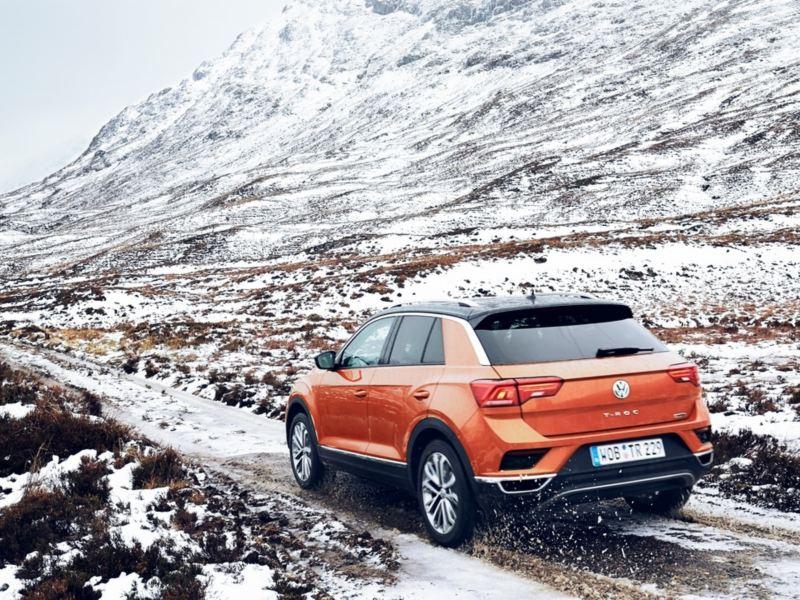 Volkswagen T-Roc naranja y negro visto desde atrás en un camino en la nieve