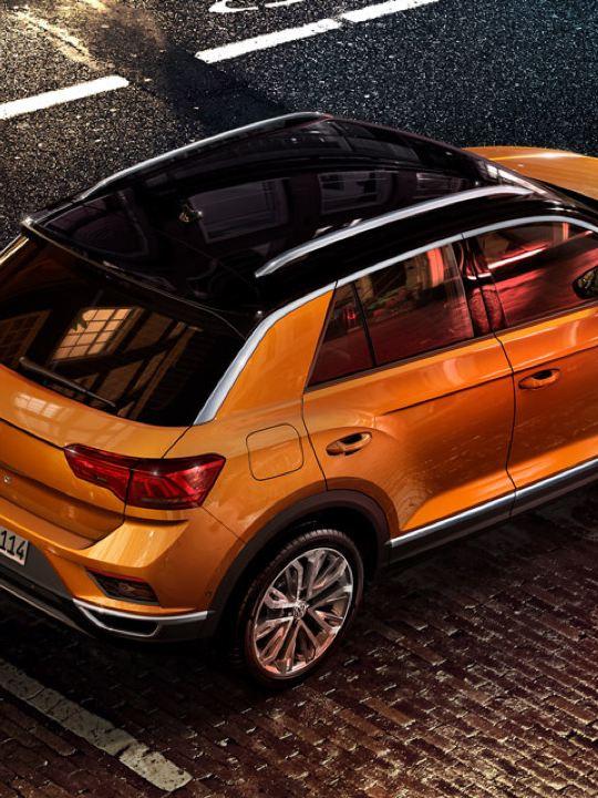 Volkswagen T-Roc naranja y negro aparcado en la ciudad visto desde arriba junto a un hombre joven