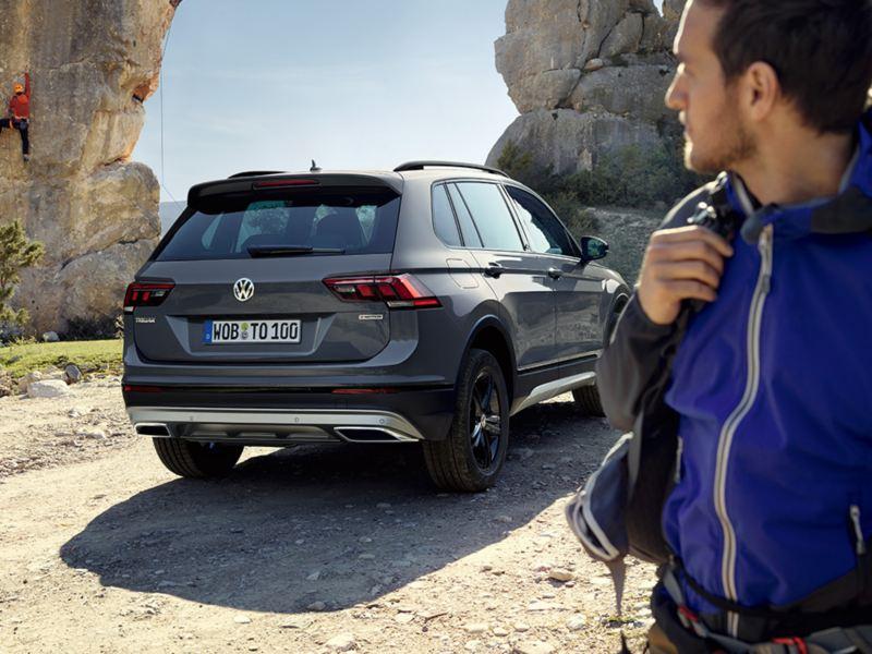 Volkswagen Tiguan visto desde atrás aparcado en un camino de montaña con dos hombres haciendo escalada