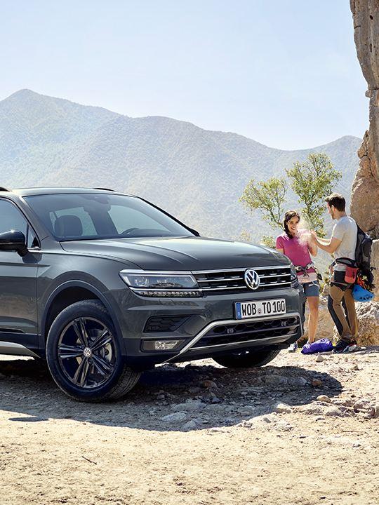 Vista frontal Volkswagen Tiguan aparcado en un camino de montaña con una pareja y un hombre haciendo escalada