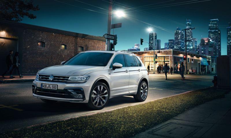 Vista frontal de un Volkswagen Tiguan blanco circulando por la ciudad de noche