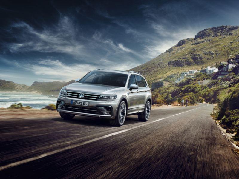 Volkswagen Tiguan Allspace visto de frente circulando por una carretera junto al mar con montañas de fondo