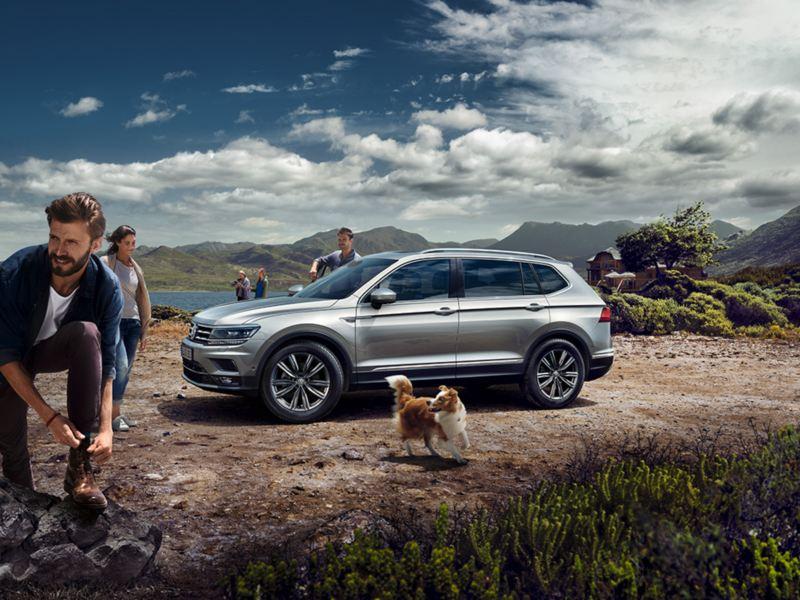 Grupo de jovenes y un perro junto a un Volkswagen Tiguan Allspace aparcado en la montaña
