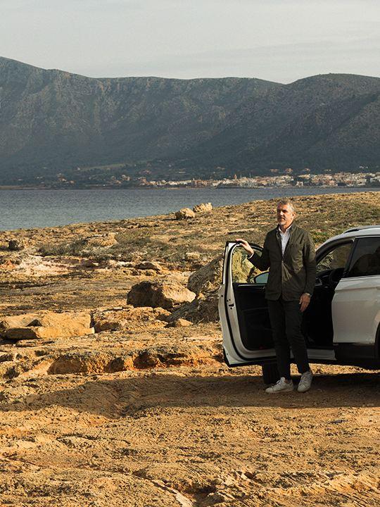 Hombre bajando de un Volkswagen Tiguan Allspace aparcado en un terreno pedregoso con vista al mar