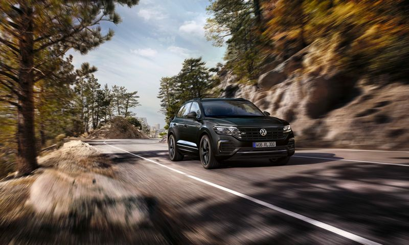 Volkswagen Touareg circulando por una carretera de montaña entre pinos