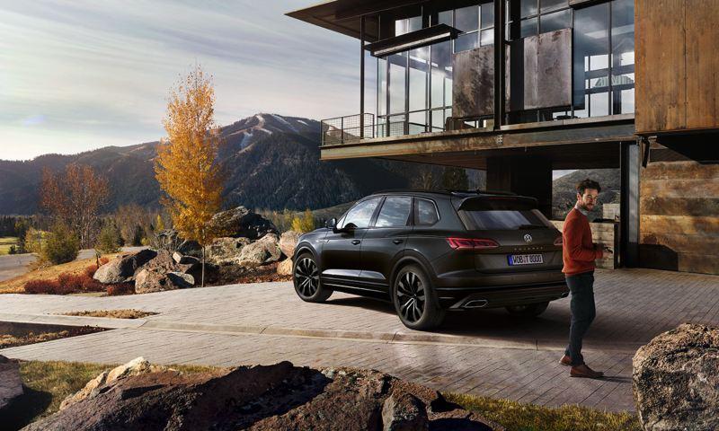 Hombre joven caminando delante de un Volkswagen Touareg negro aparcado frente a una casa