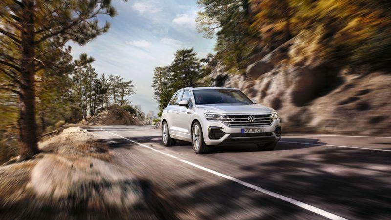 Volkswagen Tiguan blanco visto de frente circulando por una carretera de montaña