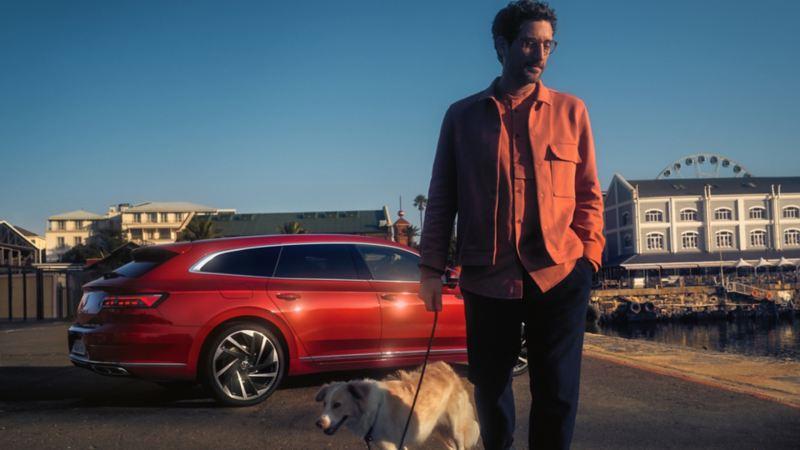 Hombre paseando a su perro dejando a sus espaldas un Arteon Shooting Brake rojo