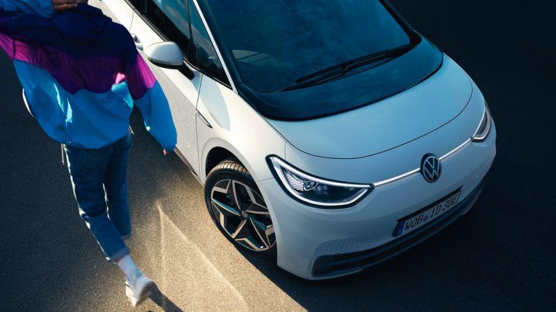 Hombre caminando al costado de un Volkswagen ID.3 blanco visto parcialmente desde arriba