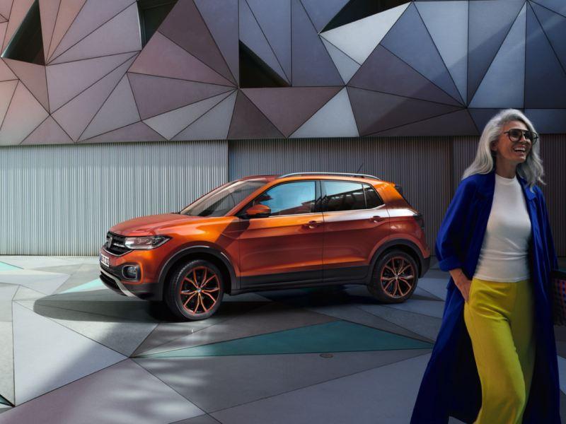 Volkswagen T-Cross naranja aparcado frente a una fachada geométrica y una mujer sonriendo en primer plano