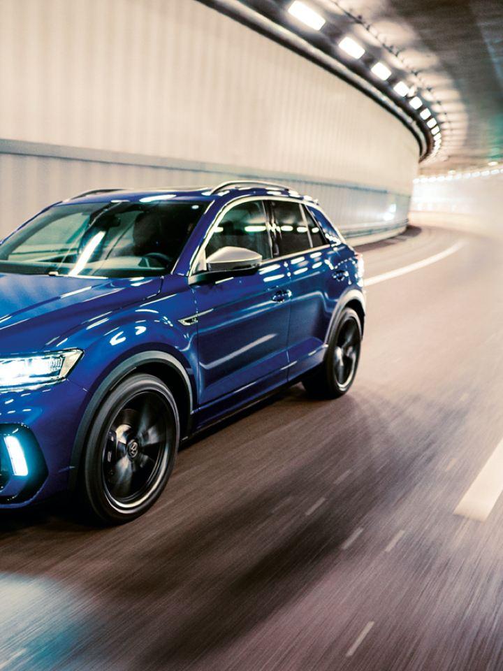 Chica apoyada en un Volkswagen T-Roc R azul aparcado en una nave