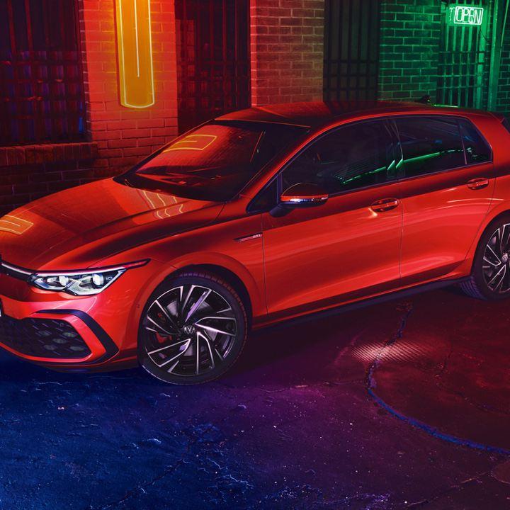Volkswagen Golf 8 GTI rojo aparcado en la calle iluminado por luces de neón