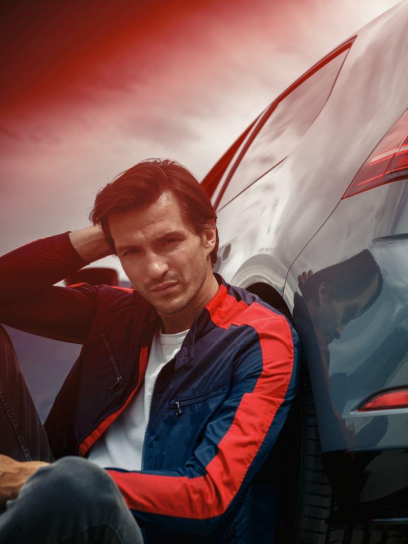 Chico mirando la cámara sentado en el suelo y apoyado en la parte trasera de un Volkswagen Golf 8 GTI